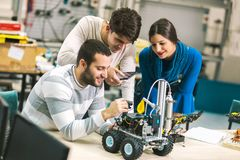 Young students of robotics preparing robot for testing. In workshop Stock Photos