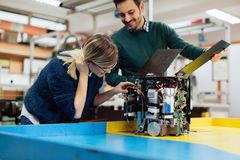 Young students of robotics preparing robot for testing royalty free stock photography