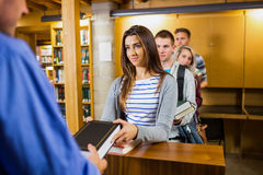 Young students in a row at the library counter Royalty Free Stock Photography