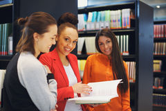 Young students sharing notes for final exams. Portrait of group of female students standing in library sharing their study notes. College students preparing for Stock Photo