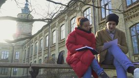Students discuss exams sitting at the bench in park near university stock video footage