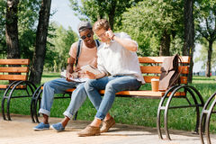 Young students sitting on bench and studying in park together Stock Photos