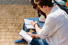 Young students sitting on bench and studying in park together Stock Photo