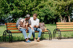Young students sitting on bench and studying in park together Royalty Free Stock Photography