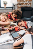 Young students sleeping on table with notebooks and digital devices Royalty Free Stock Images