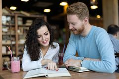 Young students spending time in coffee shop reading books Stock Photos