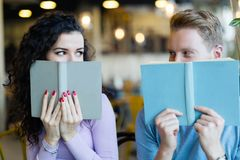 Young students spending time in coffee shop reading books Royalty Free Stock Photography