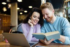 Young students spending time in coffee shop reading books royalty free stock photos