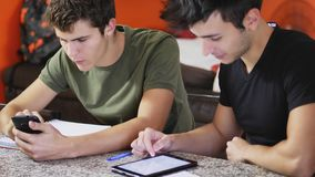 Young students studying with gadgets. Two casual male friends posing at table with devices and notepads studying together, doing homework Royalty Free Stock Photography