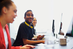 Young students using computers in classroom. Young african american men looking away smiling while in computer lab. Young students sitting at table using Royalty Free Stock Image