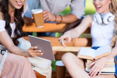 Young students using digital tablet while sitting together on bench in park. Cheerful young students using digital tablet while sitting together on bench in park Stock Images