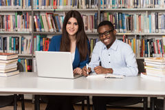 Young Students Using Their Laptop In A Library. In The Library - Handsome Two College Students With Laptop And Books Working In A High School - University Stock Images