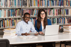 Young Students Using Their Laptop In A Library. In The Library - Handsome Two College Students With Laptop And Books Working In A High School - University Royalty Free Stock Photos