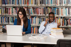 Young Students Using Their Laptop In A Library. In The Library - Handsome Two College Students With Laptop And Books Working In A High School - University Stock Photos