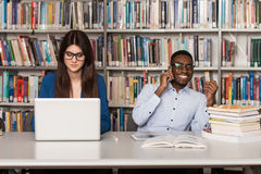 Young Students Using Their Laptop In A Library. In The Library - Handsome Two College Students With Laptop And Books Working In A High School - University Stock Photo