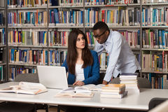 Young Students Using Their Laptop In A Library. In The Library - Handsome Two College Students With Laptop And Books Working In A High School - University Royalty Free Stock Photo
