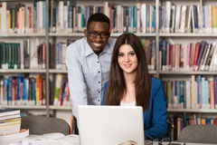Young Students Using Their Laptop In A Library. In The Library - Handsome Two College Students With Laptop And Books Working In A High School - University Stock Image