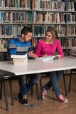 Young Students Working Together In The Library. Portrait Of Clever Students With Open Book Reading It In College Library - Shallow Depth Of Field Royalty Free Stock Image