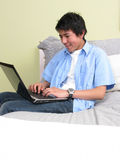 Young studying on the bed with laptop Royalty Free Stock Photography