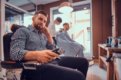 Young styilish man in checkered shirt is sitting at busy barbershop and holding trimmer for haircut. Young styilish men in checkered shirt is sitting at busy stock photos