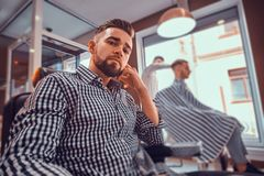 Young styilish man in checkered shirt is sitting at busy barbershop and holding trimmer for haircut. Young styilish men in checkered shirt is sitting at busy stock image