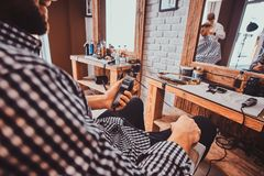 Young styilish man in checkered shirt is sitting at busy barbershop and holding trimmer for haircut. Young styilish men in checkered shirt is sitting at busy stock photo