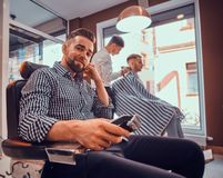 Young styilish man in checkered shirt is sitting at busy barbershop and holding trimmer for haircut. Young styilish men in checkered shirt is sitting at busy stock images