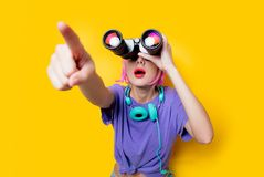 Young style girl in purple clothes with binoculars. On yellow background. Clothes in 1980s style royalty free stock photo