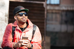 Young stylish afro american man in cap and leather jacket. Portrait of a young stylish afro american man in cap and leather jacket sitting and listening to music stock photography