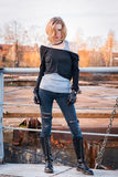 Young stylish aggressive looking woman. Lace-up boots, black lea. Ther gloves, ripped jeans, blond hair. Looking at camera. Outdoor portrait Royalty Free Stock Images
