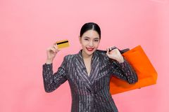 Young Stylish Asian woman carrying shopping bags and holding credit card. Beautiful fashionable woman isolated over pink Stock Photography