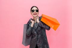 Young Stylish Asian woman carrying shopping bags and holding credit card. Beautiful fashionable woman with sunglasses isolated Royalty Free Stock Image