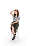 Young stylish asian woman posing while sitting on chair Royalty Free Stock Images