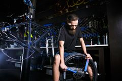 Young stylish bearded, with long hair Caucasian male mechanic worker at a bicycle workshop uses a tool for repairing Cassettes on. The rear wheel of a bicycle Royalty Free Stock Images