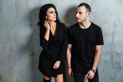 Young stylish beautiful gorgeous couple, against the gray wall loft in the studio or at home. royalty free stock photo