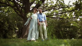 Young, stylish, beautiful pair of newlyweds walking in the park stock video