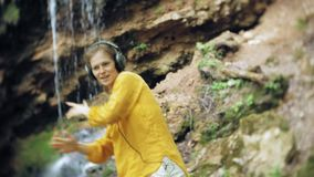 Young stylish beautiful woman, near a waterfall listening to music in large monitor headphones. 4k stock video footage