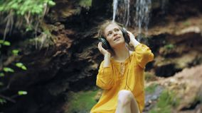 Young stylish beautiful woman, near a waterfall listening to music in large monitor headphones. 4k stock video