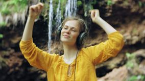 Young stylish beautiful woman, near a waterfall listening to music in large monitor headphones. 4k stock footage