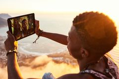 Young black man busy taking a selfie with a tablet. Young stylish black teenager busy using a tablet to take a selfie of himself on the top of a mountain trail Royalty Free Stock Images