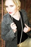 Young stylish blond woman in gray coat and pearls. Blond woman with short hair playfully holding collar of her coat ? strong eye-contact and smile stock photography
