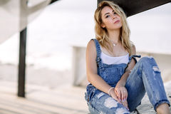 Young stylish blonde girl in denim overalls outdoors with natural daylight, a sunny day Stock Photos