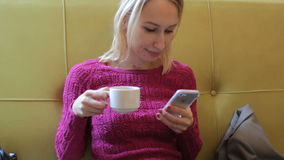 Young stylish blonde woman using smartphone in cafe drinking tea stock video footage