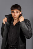 Young stylish brunet man in black shirt and black leather coat w Stock Photography