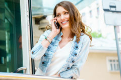 Young stylish brunette girl talking on phone outdoors Stock Photography