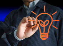 Young stylish businessman. Drawing a light bulb Royalty Free Stock Photos