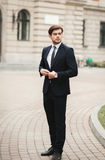 Young stylish businessman adjusting his suit, neck tie Royalty Free Stock Photo