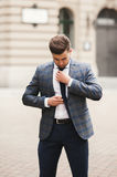 Young stylish businessman adjusting his suit, neck tie Stock Image