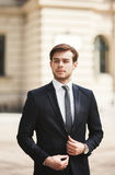 Young stylish businessman adjusting his suit, neck tie Stock Photo