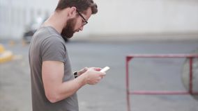 Young stylish businessman standing in the street and using smartphone. Guy with beard and glasses chatting with someone. Male browse the Internet with stock video footage